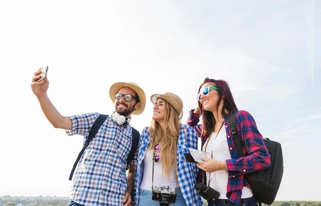 Glückliche freunde, die selfie auf smartphone an draußen nehmen Kostenlose Fotos