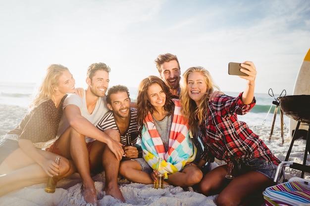 Glückliche freunde, die selfie mit smartphone nehmen Premium Fotos