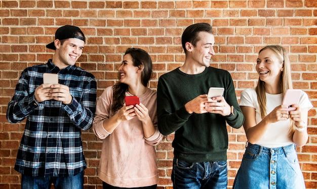 Glückliche freunde, die smartphonesocial media-konzept verwenden Premium Fotos