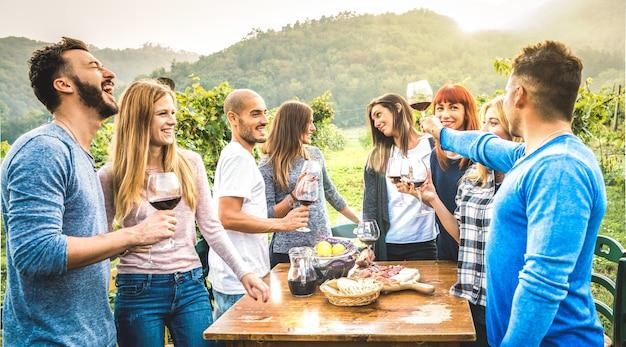 Glückliche freunde, die spaß haben, rotwein im weinberg zu trinken Premium Fotos