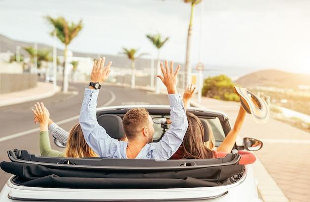 Glückliche freunde, die spaß im konvertierbaren auto bei sonnenuntergang in den ferien haben Premium Fotos