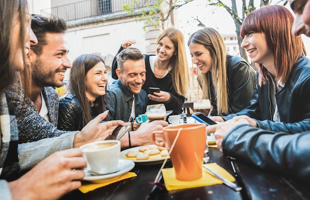 Glückliche freunde, die spaß mit intelligenten mobiltelefonen an trinkendem cappuccino des restaurants sprechen und haben Premium Fotos