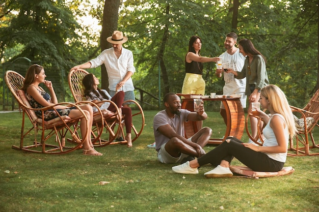 Glückliche freunde essen und trinken bier beim grillabendessen bei sonnenuntergang Kostenlose Fotos