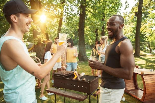 Glückliche freunde haben bier und grillparty am sonnigen tag Kostenlose Fotos