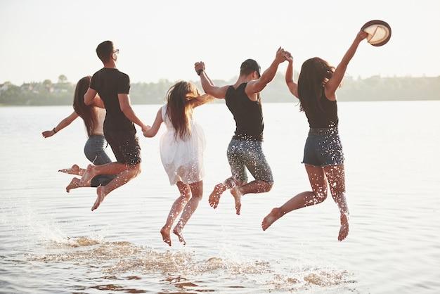 Glückliche freunde haben spaß am strand - junge leute spielen in den sommerferien im freien. Kostenlose Fotos