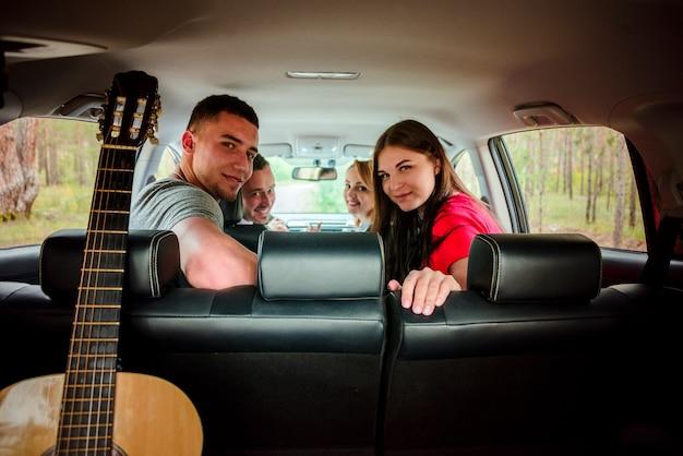 Glückliche freunde in der hinteren ansicht des autos Kostenlose Fotos