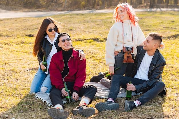 Glückliche freunde mit den bieren, die spaß zusammen auf freilichtparty haben Kostenlose Fotos