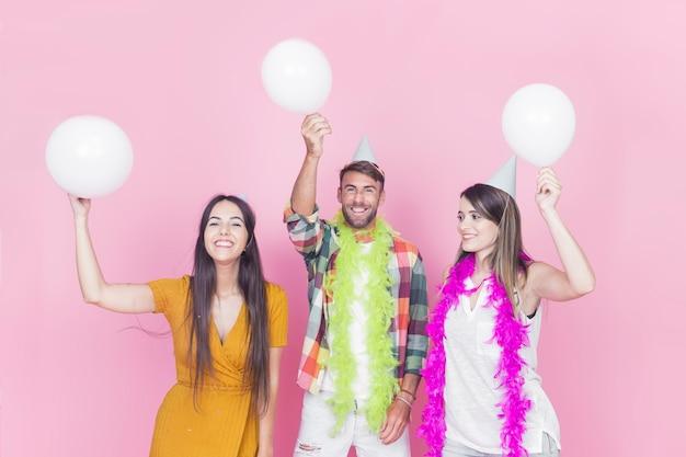 Glückliche freunde mit weißen ballonen auf rosa hintergrund Kostenlose Fotos