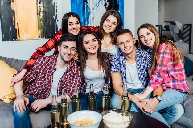 Glückliche freunde oder fußballfane, die fußball im fernsehen aufpassen und zu hause sieg feiern. popcorn essen und bier trinken. Premium Fotos