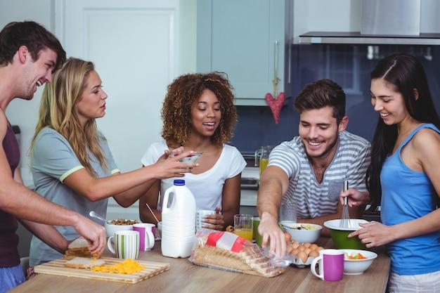 Glückliche freunde stehen am frühstückstisch Premium Fotos