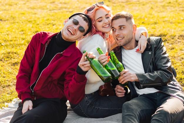 Glückliche freunde umarmen, die zusammen spaß auf picknick haben Kostenlose Fotos