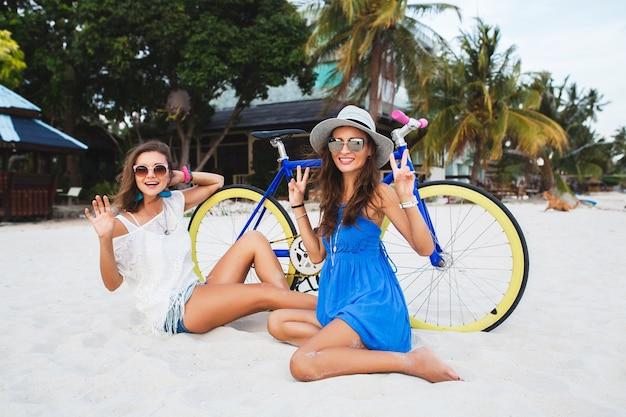 Glückliche freundinnen, die spaß am tropischen strand haben, frauen, die im urlaub in thailand mit dem fahrrad reisen Kostenlose Fotos