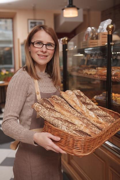 Glückliche freundliche bäckerin, die nach vorne lächelt und brotkorb in ihrem café trägt Premium Fotos