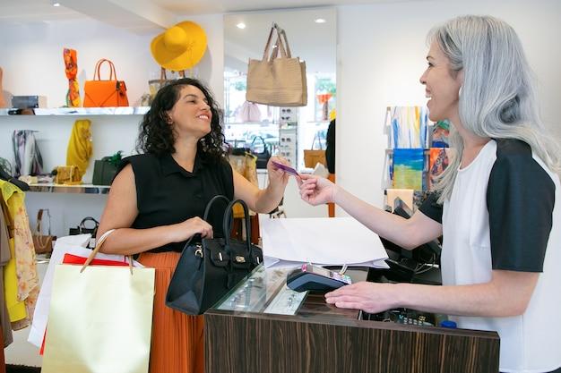 Glückliche freundliche kassiererin, die dem kunden nach der zahlung eine kreditkarte gibt, sich für den kauf bedankt und lächelt. mittlerer schuss. einkaufskonzept Kostenlose Fotos