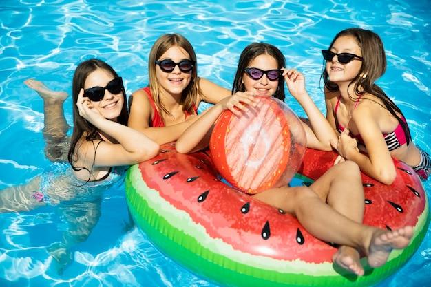 Glückliche freundmädchen im swimmingpool Kostenlose Fotos