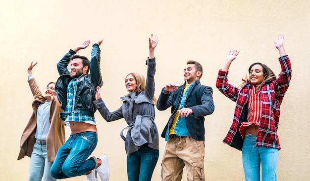 Glückliche freundmillennials, die gegen backsteinmauer springen Premium Fotos