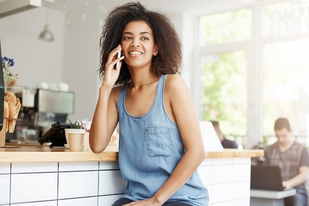 Glückliche fröhliche schöne afrikanische frau lächelnd am telefon sitzen im café. Kostenlose Fotos