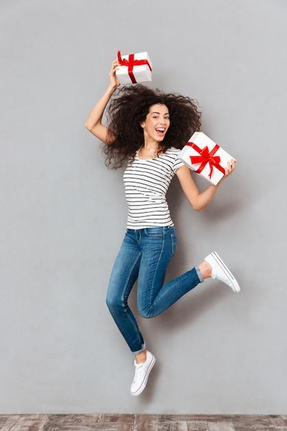 Glückliche gefühle der positiven frau in gestreiftem t-shirt und in jeans viele geschenke genießend, die in den händen halten, die den spaß haben, der über grauer wand partying ist Kostenlose Fotos
