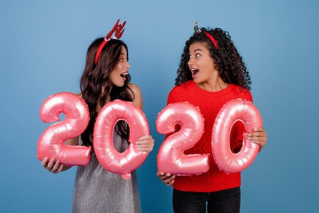 Glückliche gemischtrassige mädchen mit 2020 ballonen des neuen jahres und lustigen den feiertagsbändern lokalisiert über blau Premium Fotos