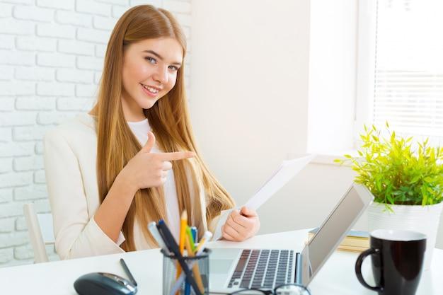 Glückliche geschäftsfrau, die an dem laptop im büro arbeitet Premium Fotos