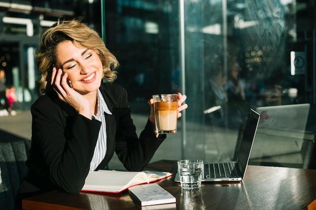 Glückliche geschäftsfrau, die auf smartphone beim halten des glases schokoladenmilchshake im restaurant spricht Kostenlose Fotos