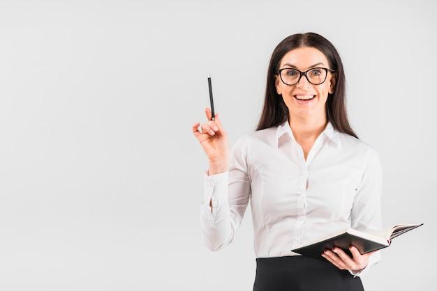 Glückliche geschäftsfrau, die mit notizbuch steht Kostenlose Fotos