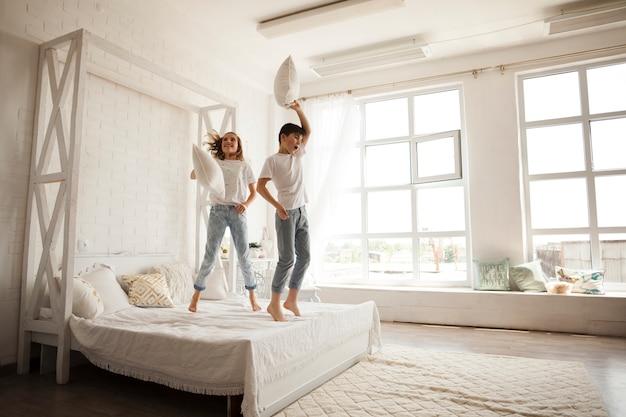 Glückliche geschwister, die auf bett im schlafzimmer springen Kostenlose Fotos