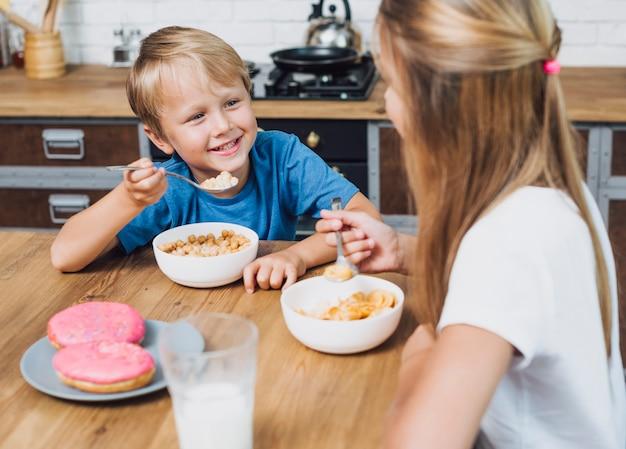 Glückliche geschwister, die einander beim essen betrachten Kostenlose Fotos