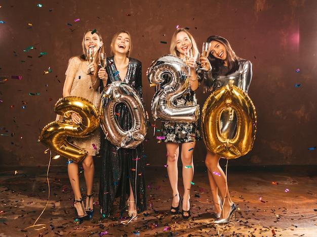 Glückliche herrliche mädchen in den stilvollen sexy party-kleidern, die gold und silber 2020 ballone halten Kostenlose Fotos