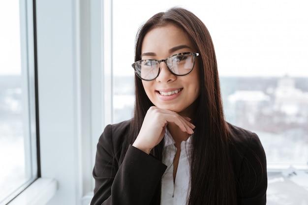 Glückliche hübsche asiatische junge geschäftsfrau, die im amt steht Premium Fotos