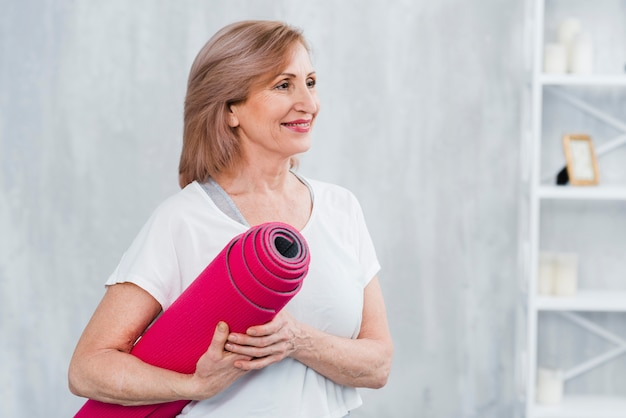 Glückliche hübsche frau, die in der hand in der hauptholdingrolle der yogamatte steht Kostenlose Fotos