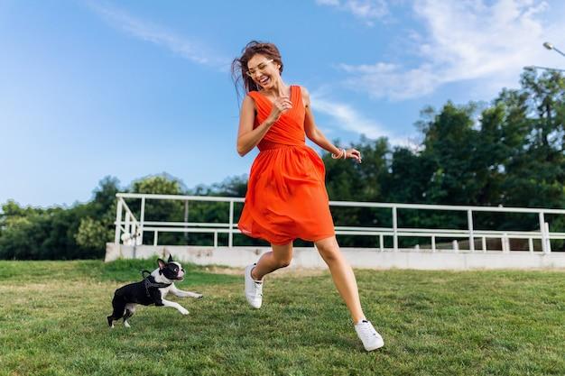 Glückliche hübsche frau im park, der mit boston-terrier-hund läuft, positive stimmung lächelt, trendiger sommerstil, orange kleid trägt, mit haustier spielt, spaß hat, bunte, aktive wochenendferien, turnschuhe Kostenlose Fotos