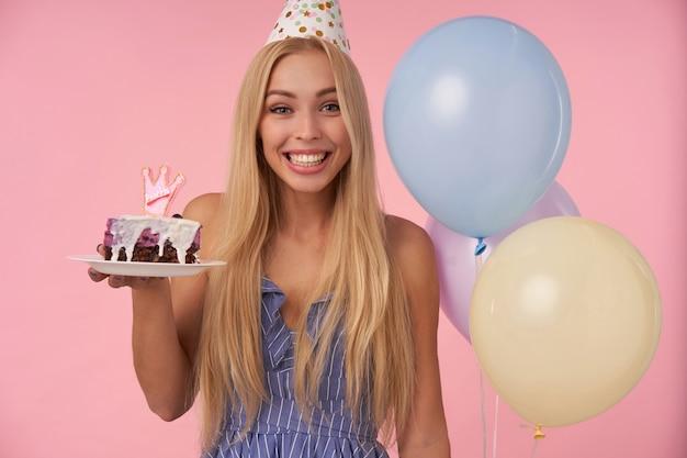 Glückliche hübsche junge blonde frau mit langen haaren, die fröhliche momente in ihrem leben während der geburtstagsfeier haben, festliche kleidung und kegelhut tragend, über rosa hintergrund mit stück kuchen stehend Kostenlose Fotos