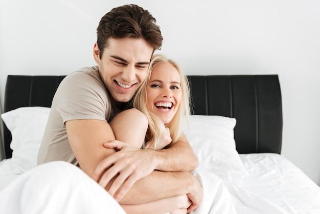 Glückliche hübsche lachende liebhaber beim sitzen im bett Kostenlose Fotos