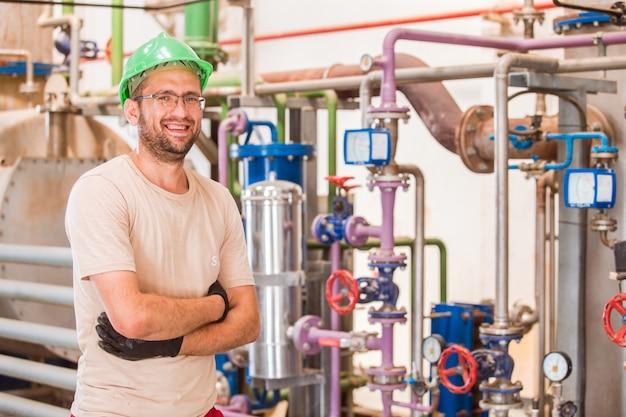Glückliche industriearbeitskraft, die innerhalb der fabrik mit stangen und rohren herum aufwirft und lächelt Kostenlose Fotos