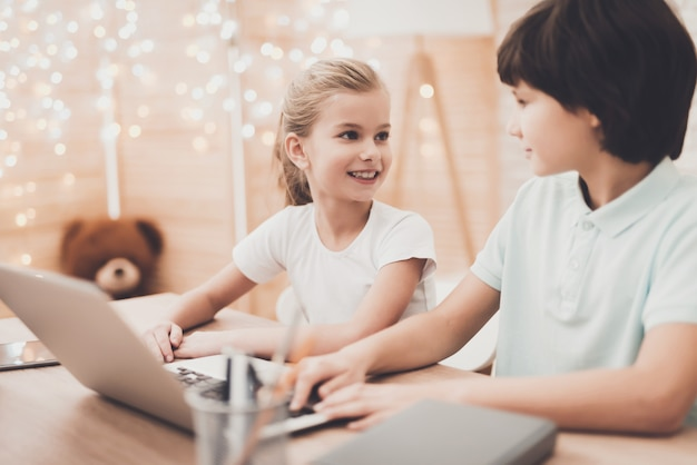 Glückliche intelligente kinder erledigen hausaufgaben am laptop. Premium Fotos