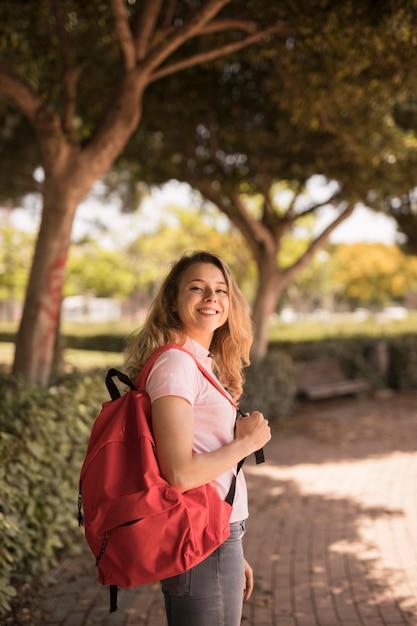 Glückliche jugendliche, die mit rucksack im park lächelt Kostenlose Fotos