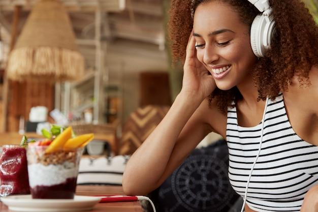 Glückliche junge afroamerikanische frau in kopfhörern sucht musik auf der internet-website zum hochladen in wiedergabeliste, verwendet modernes handy, verbunden mit wlan in gemütlicher cafeteria. hipster girl hört audio Kostenlose Fotos