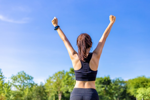 Glückliche junge asiatin, die nett oben ihre arme anhebt, nachdem sie ihr übungsprogramm an einem park im freien an einem hellen sonnigen tag abgeschlossen hat Premium Fotos