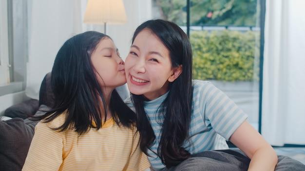 Glückliche junge asiatische familienmutter und -kind spielen zusammen auf couch zu hause. der kindertochterkuss, den ihre glückliche mutter genießt, entspannen sich, zeit im modernen wohnzimmer am abend zusammen verbringend. Kostenlose Fotos