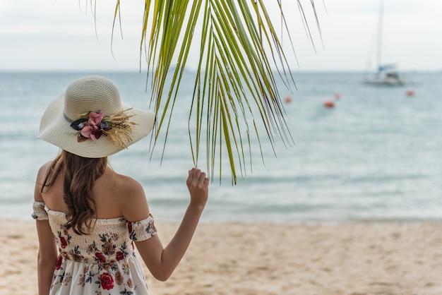 Glückliche junge asiatische frau mit dem hut, der auf strand sich entspannt Premium Fotos