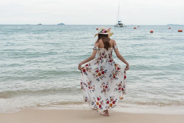 Glückliche junge asiatische frau mit hut gehend und auf sandstrand entspannend Premium Fotos