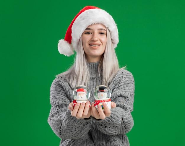 Glückliche junge blonde frau im winterpullover und in der weihnachtsmannmütze, die weihnachtsspielzeug-schneekugeln betrachten, die kamera betrachten, die fröhlich über grünem hintergrund steht Kostenlose Fotos