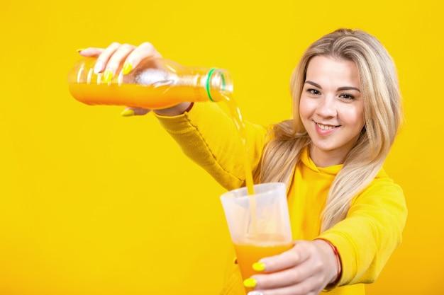 Glückliche junge blonde frau in lässigen sportlichen kleidern, die orangensaft von plastikflasche zu glas gießen, Premium Fotos