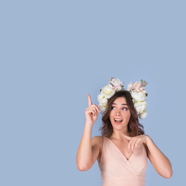 Glückliche junge dame im kleid mit blumenkranz oben zeigend Kostenlose Fotos
