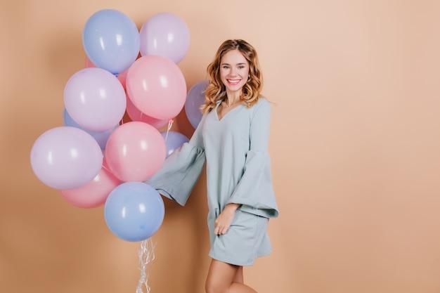 Glückliche junge dame im trendigen blauen kleid, das mit partyballons aufwirft Kostenlose Fotos