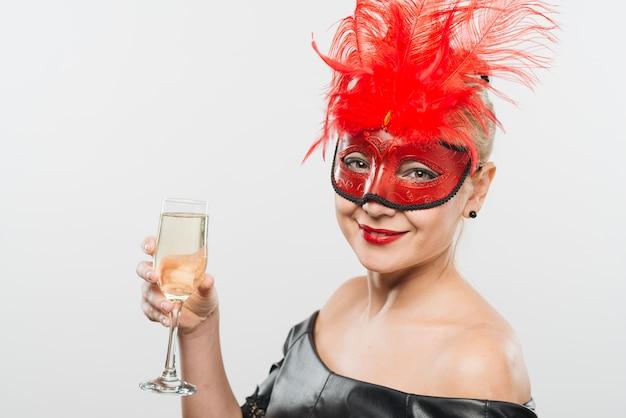 Glückliche junge dame in der maske mit den roten federn, die glas halten Kostenlose Fotos