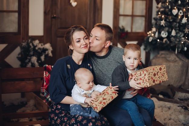 Glückliche junge erwachsene familie mit zwei jungen - kleinkind und baby, die eingewickelte weihnachtsgeschenke halten, die auf bank in gemütlichem raum mit geschmücktem weihnachtsbaum sitzen Premium Fotos