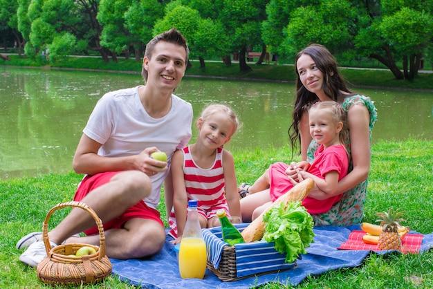 Glückliche junge familie, die draußen nahe dem see picknickt Premium Fotos