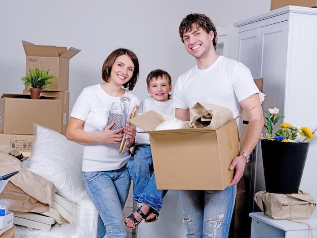 Glückliche junge familie, die in die neue wohnung zieht Kostenlose Fotos
